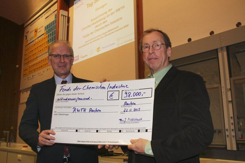 Hans-Jürgen Mittelstaedt, managing director of the NRW branch of the Chemical Industry Association, presents a symbolic cheque to RWTH Professor Bernhard Blümich.