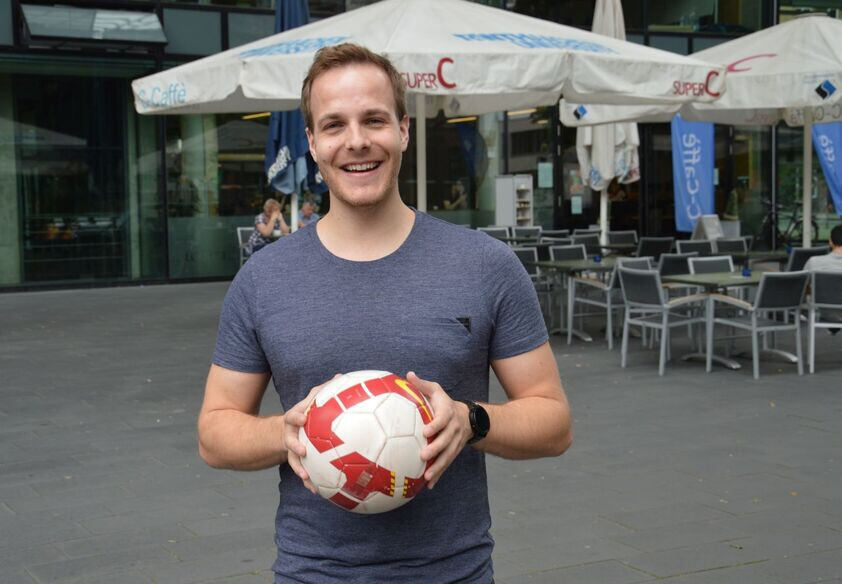 Man standing in front SuperC with football in his hands