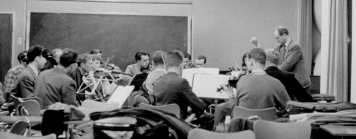 Black and white photo of an orchestra at rehearsal